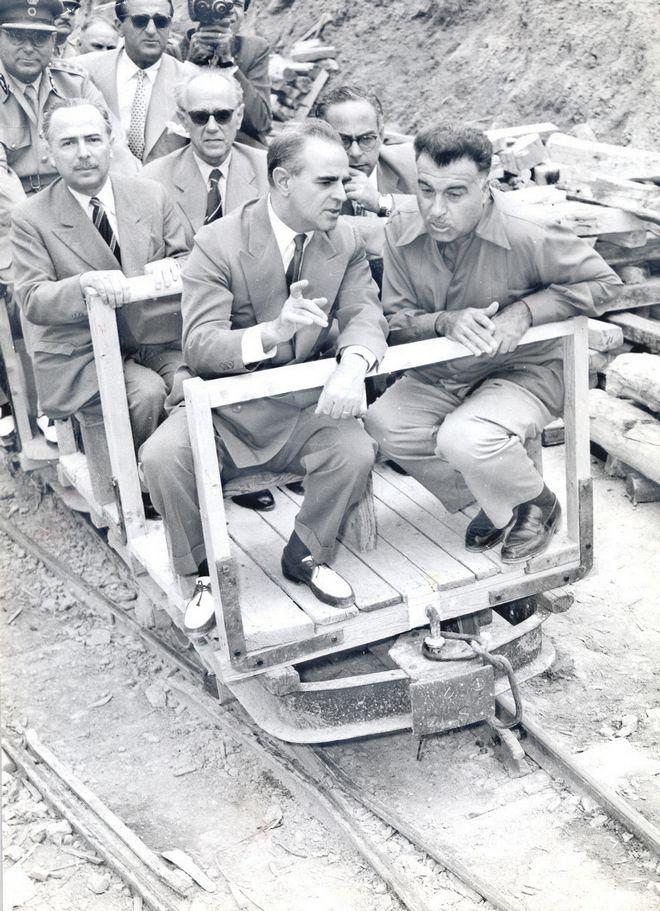 Ο Κωνσταντίνος Καραμανλής επιβαίνει στο ειδικό ξύλινο τρενάκι για να επιθεωρήσει τα έργα της Υλίκης το Σεπτέμβριο του 1956. Το έργο της υδροδότησης της Αθήνας ξεκίνησε επί υπουργίας του στο Δημοσίων Έργων και ολοκληρώθηκε επί πρωθυπουργίας του