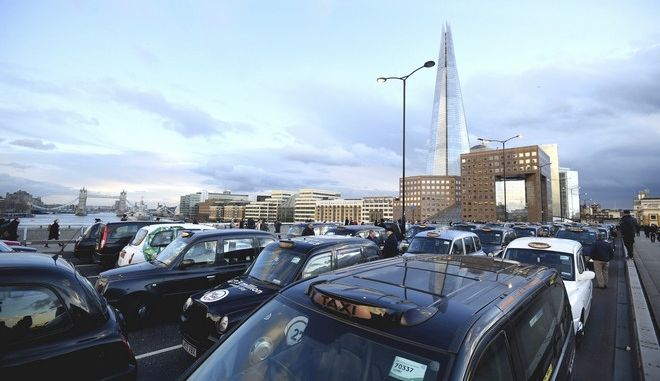 Black cab drivers take part in a protest against Transport for London and Uber, on London Bridge, in the City of London, Thursday Jan. 18, 2018, with the Shard in the background, and Tower Bridge rear left. The protest is part of a week-long campaign by licensed black cab drivers calling for the total immediate revocation of Uber's licence to run a taxi service in the capital. (Kirsty O'Connor/PA via AP)