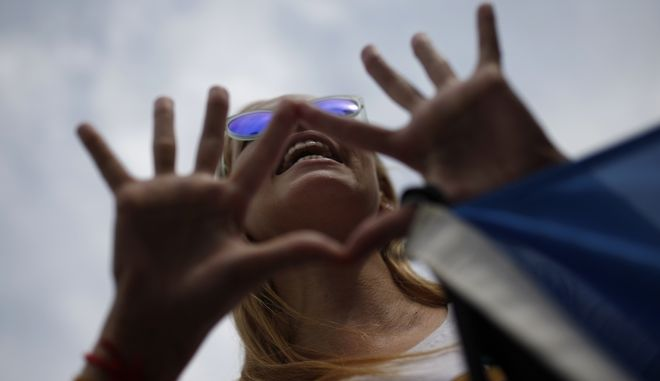 A woman shouts slogans during a small gathering to protest against violence against women, in Madrid, Monday, June 19, 2017. Protesters demanded more public funds to reinforce programs to fight against violence against women and promote gender equality. (AP Photo/Francisco Seco)