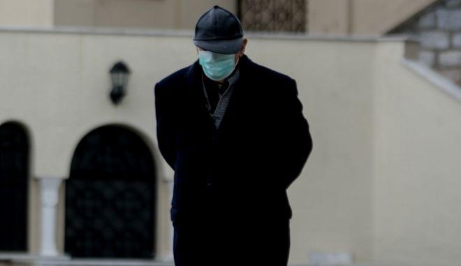 Ηλικιωμένος με μάσκα έξω από εκκλησία