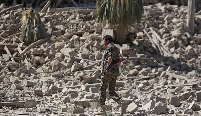 A Houthi Shiite fighter walks amid the rubble of the Republican Palace that was destroyed by Saudi-led airstrikes, in Sanaa, Yemen, Wednesday, Dec. 6, 2017. (AP Photo/Hani Mohammed)