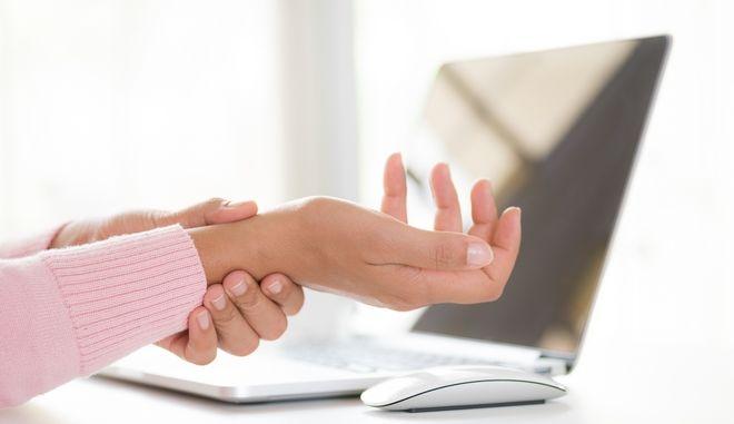Γυναίκα πιάνει το χέρι της από τον πόνο
