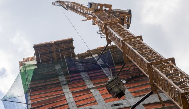 A crane lifts construction materials to the top of a high rise building under construction on 50th Street between Third and Lexington Avenues, Thursday, Aug. 10, 2017, in New York. The New York City Council approved a rezoning for a section of Midtown Manhattan from east 39th to east 57th Streets and from the east side of Third Avenue to the west side of Madison Avenue allowing developers to build larger office towers if they contribute funding for public improvements. (AP Photo/Mary Altaffer)