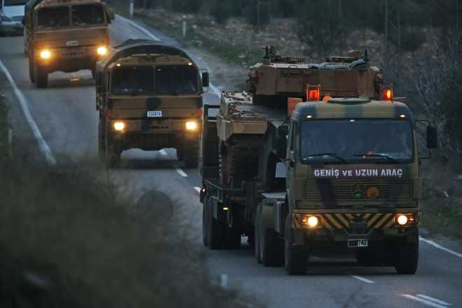Trucks, one transporting a Turkish Army tank, form a convoy on the outskirts of Kilis, Turkey, near the border with Syria, Sunday, Jan. 21, 2018. Turkey's ground troops entered the enclave of Afrin in northern Syria on Sunday and were advancing with Turkish-backed Syrian opposition forces in their bid to oust U.S.-allied Syrian Kurdish forces from the region. (AP Photo/Lefteris Pitarakis)