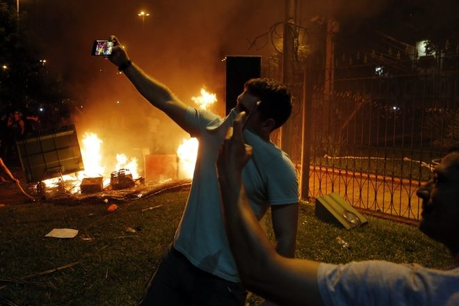 Two men pose for selfies during a protest against presidential re-elections at Congress,  in Asuncion, Paraguay, Friday, March 31, 2017. A majority in Paraguay's Senate has approved a constitutional amendment allowing the re-election of a president to a second term in a move termed illegal by opposition members. (AP Photo/Jorge Saenz)