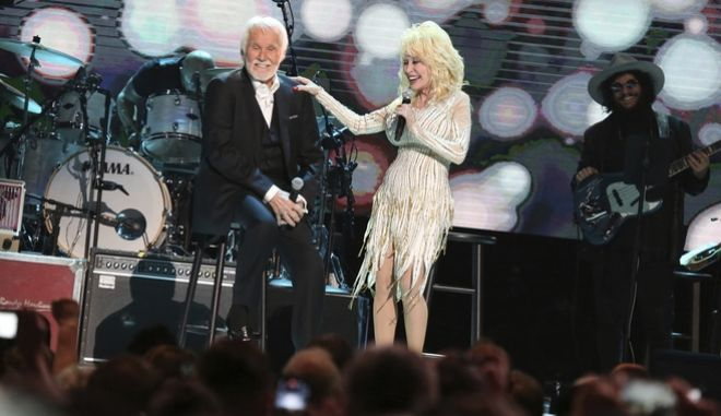 """Kenny Rogers, left, and Dolly Parton share a few stories at """"All In For The Gambler: Kenny Rogers' Farewell Concert Celebration"""" at Bridgestone Arena on Wednesday, Oct. 25, 2017, in Nashville, Tenn. (Photo by Laura Roberts/Invision/AP)"""