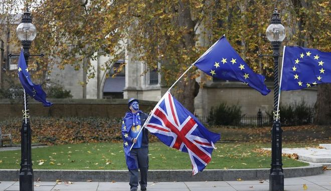 "An anti Brexit, pro European Union campaigner waves flags near Parliament in London, Wednesday, Nov. 22, 2017.  Britain's Treasury chief has little room to maneuver Wednesday as he reveals his spending plans to a nation bracing for the shock of Brexit. While Philip Hammond is promising to tackle a bleak economic outlook ""head on,"" a slowing economy and stubborn deficit mean there is little money available to increase spending in the face of demands from teachers, firefighters, the National Health Service and the military.  (AP Photo/Kirsty Wigglesworth)"