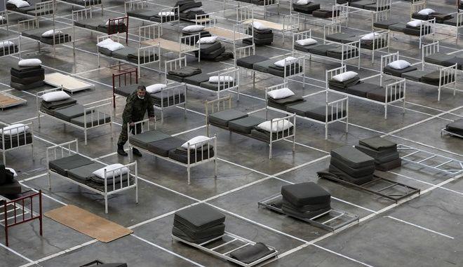 Σέρβος στρατιώτης επιθεωρεί κρεβάτια για πιθανά κρούσματα κορνοϊού, στο εσωτερικό της έκθεσης του Βελιγραδίου