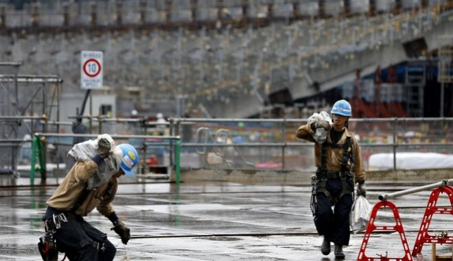 Laborers work at a construction site of the new national stadium in Tokyo, Tuesday, Sept. 12, 2017. Tokyo's main Olympic stadium is starting to take shape as structures of what will become spectator stands are being installed after 10 months of underground foundation work. (AP Photo/Shizuo Kambayashi)