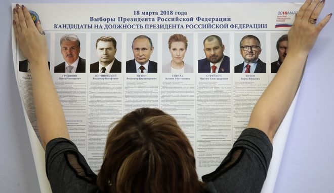 A polling station employee hangs a list of candidates for the 2018 Russian presidential election during preparations for the election at a polling station in St.Petersburg, Russia, Friday, March 16, 2018. On March 18 presidential elections will be held in Russia. (AP Photo/Dmitri Lovetsky)