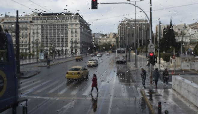 Seen through the rain streaked window of a tourist bus, a woman crosses a street during rainfall in central Athens Friday, April 12, 2019. (AP Photo/Petros Giannakouris)