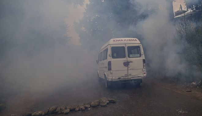 An ambulance makes it way through tear gas smoke during a protest after the funeral procession of Akeel Ahmed Bhat, a teenage boy in Haal village, about 47 Kilometers (29 miles) south of Srinagar, Indian controlled Kashmir, Wednesday, Aug. 2, 2017. A fresh strike called by anti-India separatists to protest the killings of two top rebels and a civilian shut down disputed Kashmir Wednesday while a teenage boy died a day after he was wounded by government forces. (AP Photo/Dar Yasin)