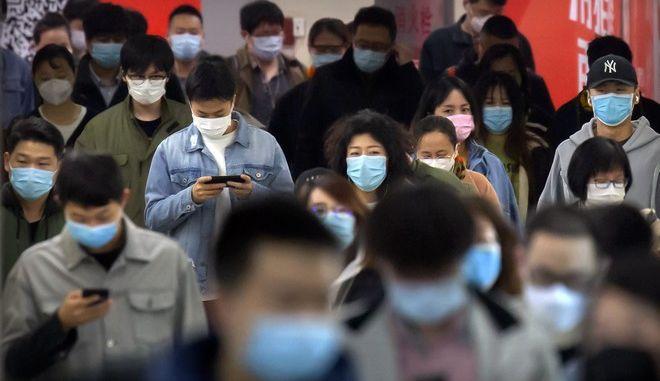 Πολίτες της Κίνας περπατούν με μάσκες