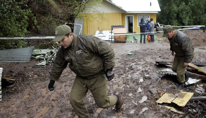 Police officers inspect next to a house destroyed by a landslide on the road to Farallones Ski Center, outskirts of Santiago, Monday, Sept. 7, 2009. At least two people died, officials said.  (AP Photo/Santiago Llanquin)