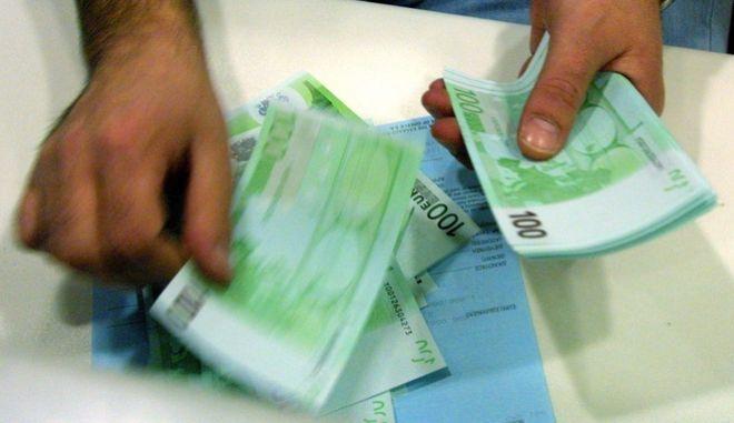 Ταμίας τράπεζας μετράει χαρτονομίσματα.