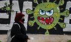Γυναίκα με μάσκα περπατά μπροστά από γκράφιτι για τον κορονοϊό