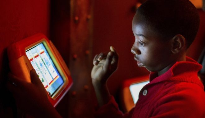 In this Sunday, Nov. 20, 2016, photo, Brandon Mack, 13, plays a sled game on an iPad inside the Adventure to Santa, a DreamWorks DreamPlace experience at North Point Mall, in Alpharetta, Ga. The Santa experience has gotten a makeover as many malls install shows and games they hope will lure shoppers who are buying more online. (AP Photo/Branden Camp)