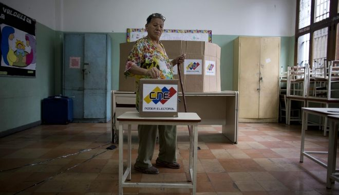 A woman casts her ballot at a polling station during Mayoral Elections in Caracas, Venezuela, Sunday, Dec.10, 2017. Venezuelans will choose hundreds of mayors on Sunday in elections pitting candidates backed by President Nicolas Maduro against a fractured opposition still bruised by a poor showing in recent gubernatorial voting.(AP Photo/Ariana Cubillos)