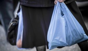 Ηλικιωμένη γυναίκα κρατά στα χέρια της πλαστικές σακούλες