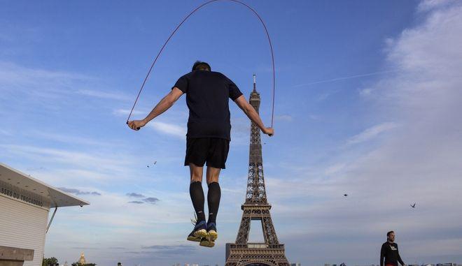 Άνδρας κάνει ασκήσεις σε πλατεία κοντά στον Πύργο του Άιφελ