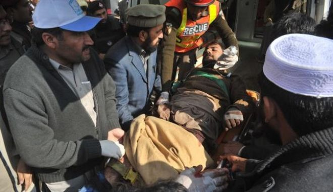 Pakistani rescuers shift an injured man into a hospital following an attack by gunmen at Bacha Khan university in Charsadda, about 50 kilometres from Peshawar, on January 20, 2016. At least 21 people died in an armed assault on a university in Pakistan on January 20, where witnesses reported two large explosions as security forces moved in under dense fog to halt the bloodshed. AFP PHOTO /Hasham AHMED / AFP / HASHAM AHMED        (Photo credit should read HASHAM AHMED/AFP/Getty Images)