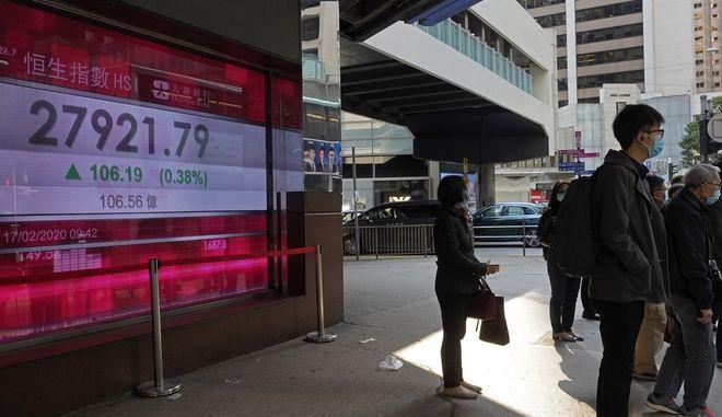 Άνθρωποι μπροστά από πίνακα χρηματιστηριακών συναλλαγών