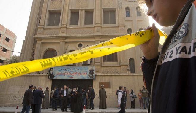 A boy holds the yellow label surrounding the site in front of Mar Mina church, in Helwan, Cairo, Egypt, Friday, Dec. 29, 2017, where several people have been killed in a shootout outside the church. (AP Photo/Amr Nabil)