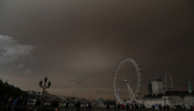 The sky over the London Eye is bathed in a dull orange sky in London, Monday, Oct. 16, 2017. The unusual hue of the sky was thought to be due to the remnants of the Hurricane  Orphelia dragging in tropical air and dust from the Sahara. (AP Photo/Frank Augstein)