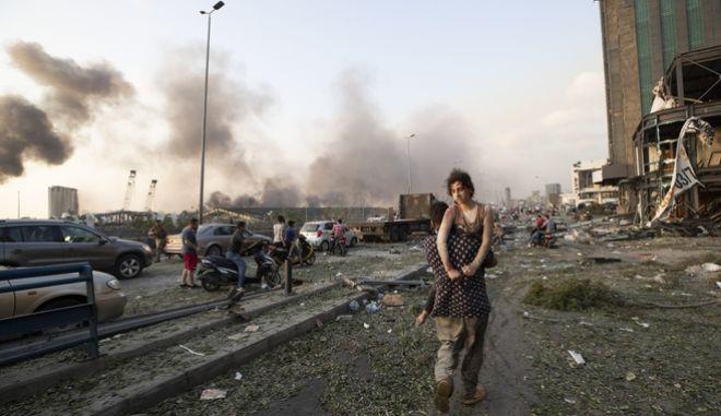 Ένας άνδρας κουβαλά μια γυναίκα ανάμεσα στα συντρίμια των καταστροφικών εκρήξεων που σημειώθηκαν στη Βηρυτό