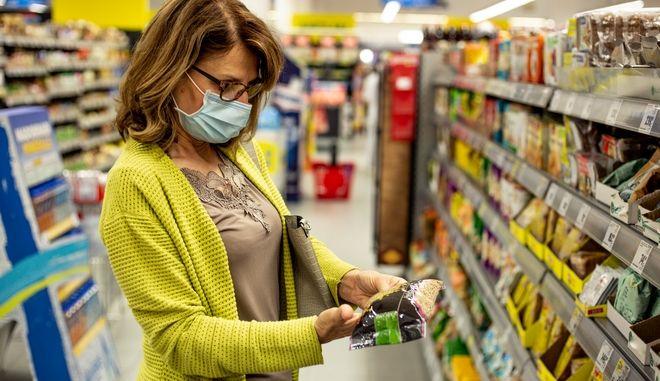 Γυναίκα με μάσκα σε σούπερ μάρκετ