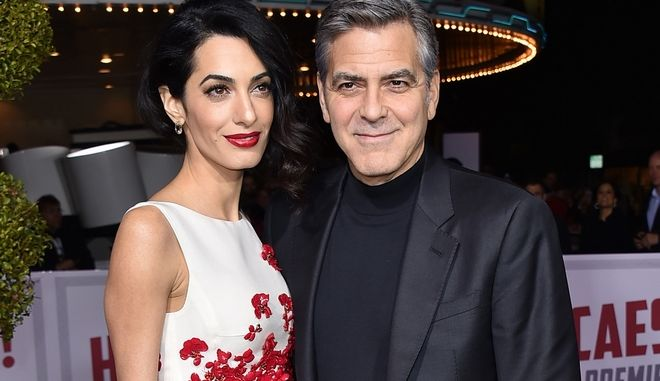 """FILE - In this Feb. 1, 2016 file photo, Amal Clooney, left, and George Clooney arrive at the world premiere of """"Hail, Caesar!"""" in Los Angeles.  The two wed on Sept. 27, 2014, in Venice, Italy. (Photo by Jordan Strauss/Invision/AP, File)"""