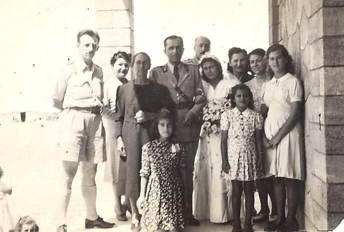 Ο γάμος του πατέρα μου και της μητέρας μου, το 1942 στην Ισμαηλία της Αιγύπτου. Δεξιά, στον τοίχο με το λευκό φόρεμα, η μεγάλη αδερφή της μητέρας μου, Μαρία και το κοριτσάκι μπροστά δεξιά, η μικρή αδερφή, Ελπίδα. Δίπλα στον πατέρα μου, με το σκούρο φόρεμα, η μητέρα των κοριτσιών και γιαγιά μου, Δέσποινα.