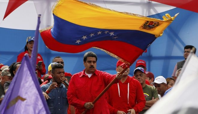 Venezuela's President Nicolas Maduro waves the Venezeulan flag during a rally in Caracas, Venezuela, Thursday, July 27, 2017. Maduro has provoked international outcry and enraged an opposition demanding his resignation with his push to elect an assembly that will rewrite the constitution. Sunday's election will cap nearly four months of political upheaval that has left thousands detained and injured and at least 100 dead. (AP Photo/Ariana Cubillos)
