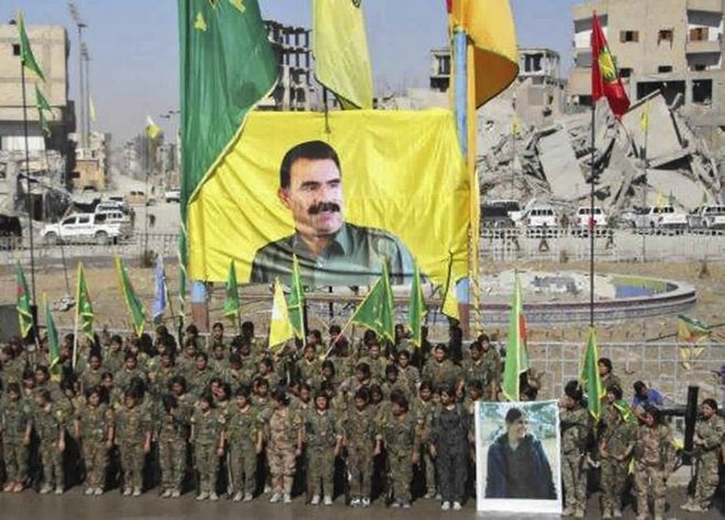 This frame grab from a video released Thursday, Oct. 19, 2017 provided by Ronahi TV, a Kurdish TV channel media outlet that is consistent with independent AP reporting, shows members of a Kurdish female militia, the Women's Protection Units, under a portrait of their jailed leader, Abdullah Ocalan, as they celebrate victory against the Islamic State group, in Raqqa, Syria. The militia that took part in freeing the northern Syrian city of Raqqa from the Islamic State group said it will continue the fight to liberate women living under the extremist group's brutal rule. (Ronahi TV, via AP)