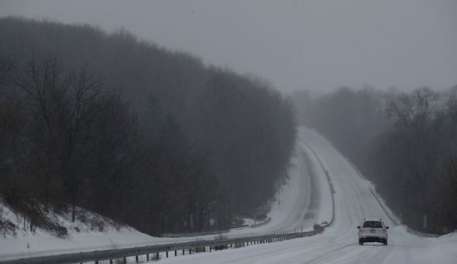 A car drives down US 30 through a winter snow storm, Tuesday, March 14, 2017, in Valley Township, Pa. (AP Photo/Matt Slocum)