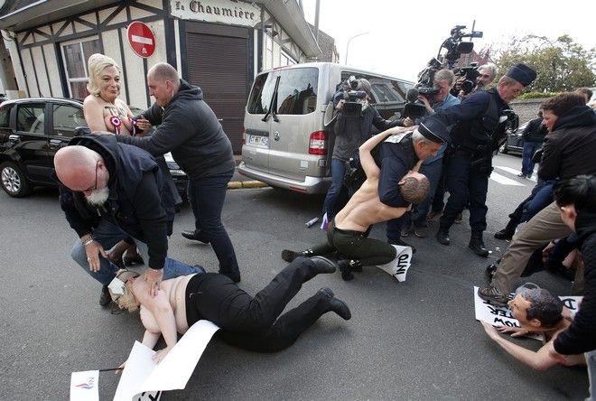 Femen activists with masks, including one wearing a mask of Marine Le Pen, top left, are detained as they demonstrate in Henin-Beaumont, northern France, where far-right leader and presidential candidate Le Pen will vote, during the first round of the French presidential election, Sunday, April 23, 2017. French voters began casting ballots for the presidential election Sunday under heightened security in a tense first-round poll that's seen as a test for the spread of populism around the world. (AP Photo/Michel Spingler)