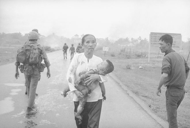 Anguished Vietnamese woman carries her napalm burned child down route one, moments after a misplaced napalm bomb strike injured and killed a score civilians and soldiers. Vietnamese troops were fighting two battalions of North Vietnamese troops on route one at the outskirts of Trang Bang, 25 miles NW of Saigon, South Vietnam on June 8, 1972. (AP Phot/Nick Ut )