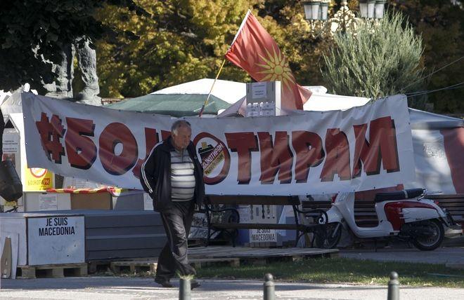 Άνδρας περνά μπροστά από εκλογικό κέντρο με πανό που καλεί τους πολίτες να μποϊκοτάρουν το δημοψήφισμα. 27 Σεπτεμβρίου 2018