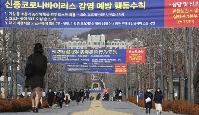 Άνθρωποι περπατούν κάτω από πανό σχετικά με προφυλάξεις κατά του νέου κορωναϊού στο Πανεπιστήμιο Yonsei στη Σεούλ της Νότιας Κορέας