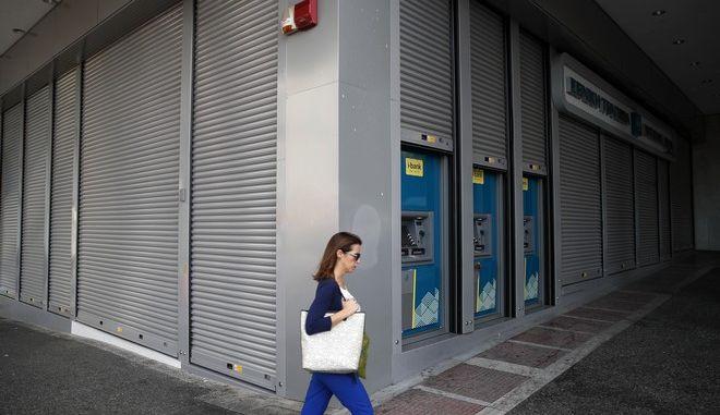 Γυναίκα περνάει έξω από κλειστή τράπεζα στην Αθήνα