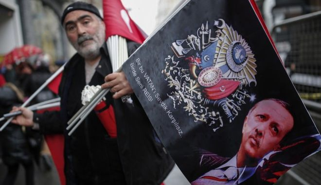 """A vendor holds Turkish flags and banners with pictures of Turkish President Recep Tayyip Erdogan, for sale during a protest outside the Dutch consulate in Istanbul, Sunday, March 12, 2017. Erdogan says he appropriately accused the Dutch government of """"Nazism and fascism,"""" saying only those types of regimes would bar foreign ministers from traveling within their countries. Erdogan also said during a live televised address on Sunday that the Netherlands would """"pay the price"""" for sacrificing its ties with a NATO ally to upcoming elections there. (AP Photo/Emrah Gurel)"""
