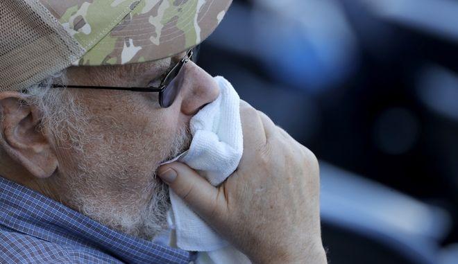 Θεατής χρησιμοποιεί πετσέτα για να καλύψει το στόμα του