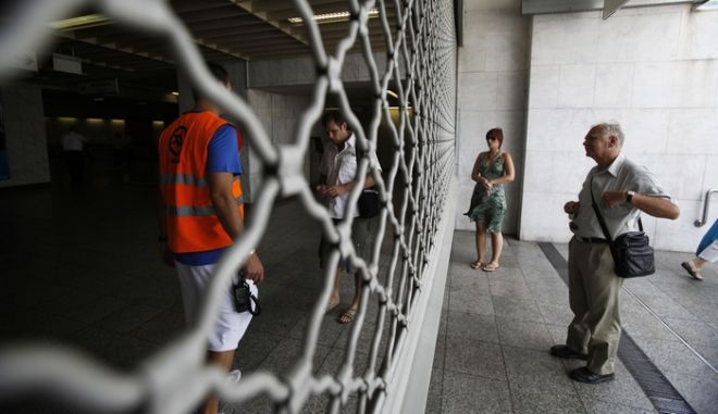 An employee at the Athens Metro stands inside the shuttered entrance of the subway at Athens' main Syntagma Square during a four-hour work stoppage, on Wednesday, Sept. 7, 2011. Strike-minded unions are fiercely opposed to sweeping labor reforms announced by the government this week. Under pressure from international rescue lenders, Greece is planning to suspend public servants with reduced pay in an effort to slash state spending and overcome serious delays in its deficit-reduction program. (AP Photo/Kostas Tsironis)