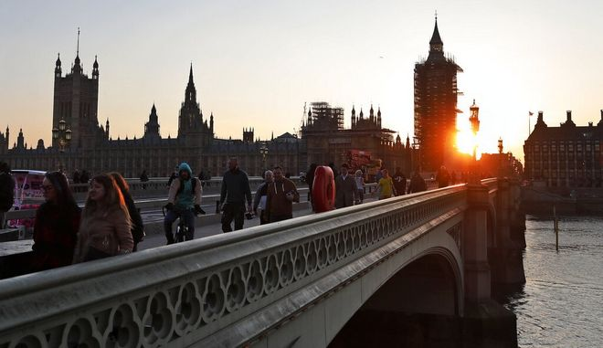 Pedestrians cross Westminster Bridge during sunset in London, Tuesday, March 23, 2021. One year since Prime Minister Boris Johnson announced UK-wide lockdown to slow the fast-spreading coronavirus, a national day of reflection is being organized to remember the people who died after contracting COVID-19.  The U.K. has registered more than 126,000 virus-related deaths, the highest pandemic death toll in Europe and the fifth-highest worldwide.(AP Photo/Frank Augstein)