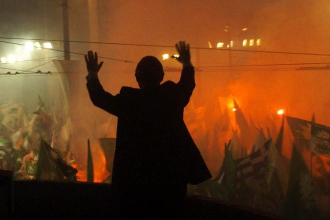 Premier Costas Simitis, silhouetted, waves to supporters of his Socialist party during an election rally in central Athens on Friday, April 7, 2000.