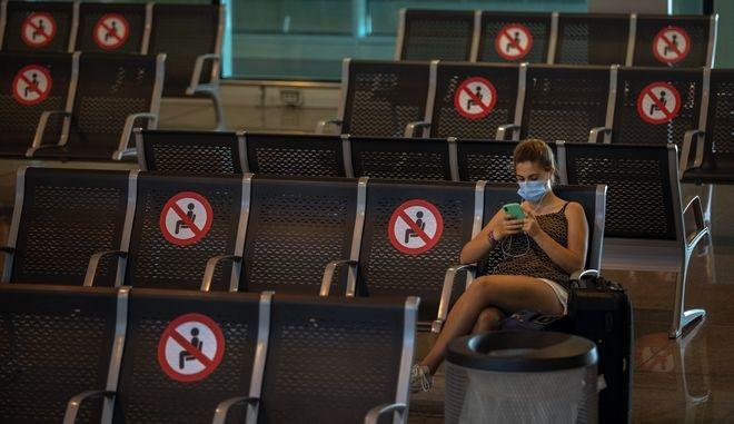 Γυναίκα σε αίθουσα αναχωρήσεων στο αεροδρόμιο