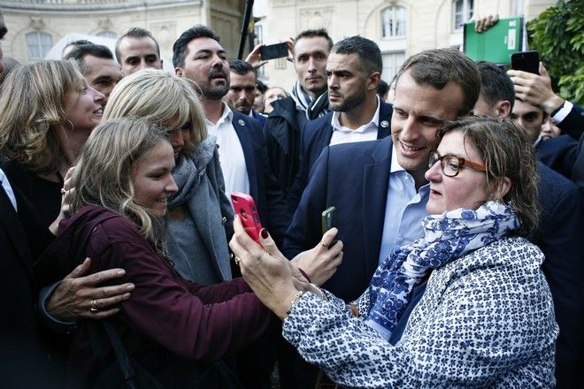French President Emmanuel Macron,right, and his wife Brigitte, left, pose for a selfie with visitors in the Elysee presidential palace in Paris, Sunday, Sept. 17, 2017 as part of the 34th edition of France's heritage open days. The national buildings and administrations of France are open to the public for the Heritage Days weekend. (AP Photo/ Thibault Camus, Pool )