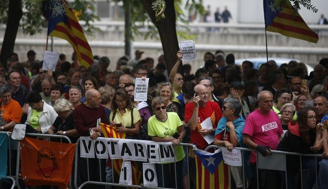 "Protesters gather in support of Catalan officials that were arrested at the courthouse in Barcelona, Spain, Friday, Sept. 22, 2017.A demonstration against police raids and arrests of officials as part of a crackdown on a planned Catalan independence referendum ended after those arrested were released. Banners reads in Catalan: ""We vote to be free"". (AP Photo/Manu Fernandez)"