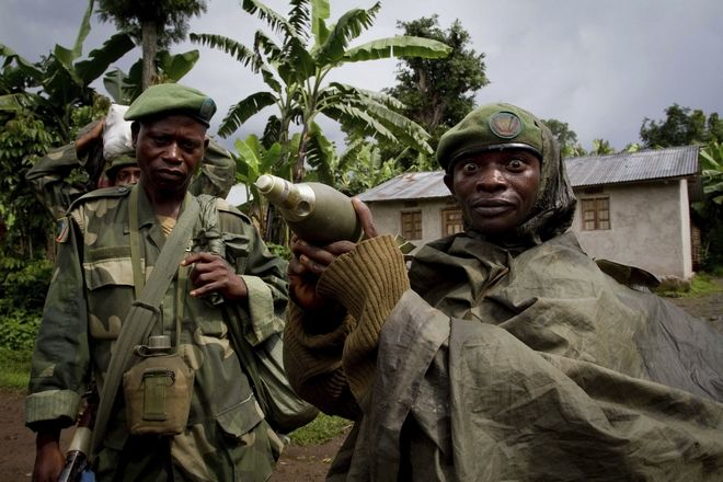 FILE - In this May 17, 2012 file photo, a Congolese government army soldier displays a mortar round after his unit returned from fighting against rebel forces, in Kinyamahura, Democratic Republic of Congo. Increased violence and corruption in central Africa could be the result of the recent decision by the U.S. Securities and Exchange Commission not to enforce a rule requiring American companies to report their use of conflict minerals, warn Congolese civic groups, rights groups and U.S. senators. In April 2017 the SEC said it will no longer enforce the 2012 rule that requires companies to verify that products using valuable African minerals don't benefit armed groups.(AP Photo/Marc Hofer-File)