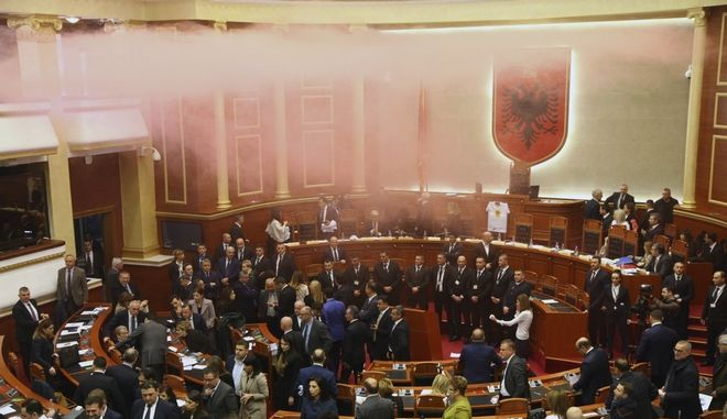 Albania's opposition lawmakers throw smoke bombs inside the parliament during the election of a temporary prosecutor general, which they consider to be unconstitutional in Tirana, Monday, Dec. 18, 2017. Albanian police have clashed with opposition supporters trying to force their way into and disrupt a session of parliament. (AP Photo)